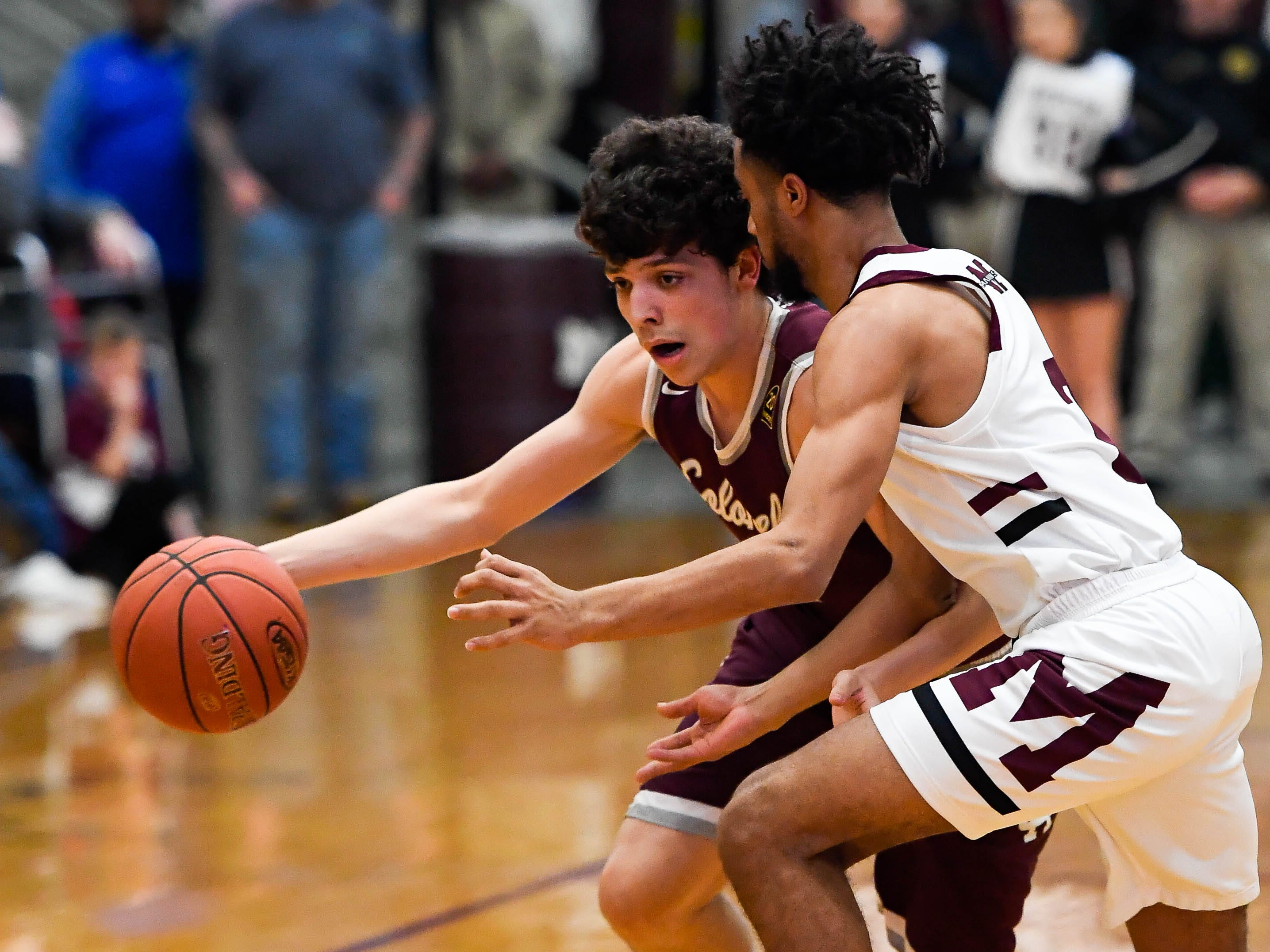 Henderson's Corey Stewart (1) drives against Madisonville's J.D. Gilbert (2) as the Henderson County Colonels play the Madisonville Maroons in the Boys 2nd Region basketball semi-finals Friday in Hansen, March 1, 2019.