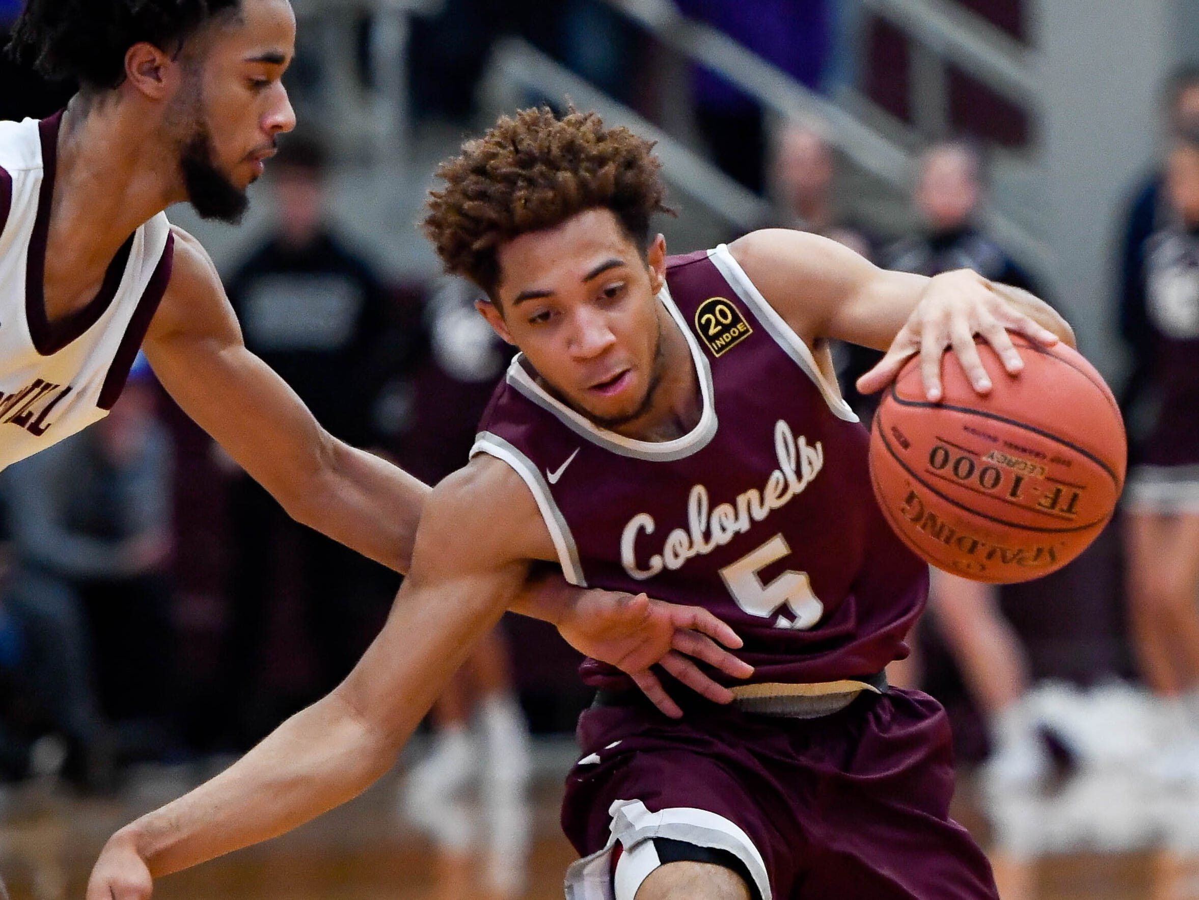 Henderson's Edmund Brooks (5) drives against Madisonville's J.D. Gilbert (2) as the Henderson County Colonels play the Madisonville Maroons in the Boys 2nd Region basketball semi-finals Friday in Hansen, March 1, 2019.