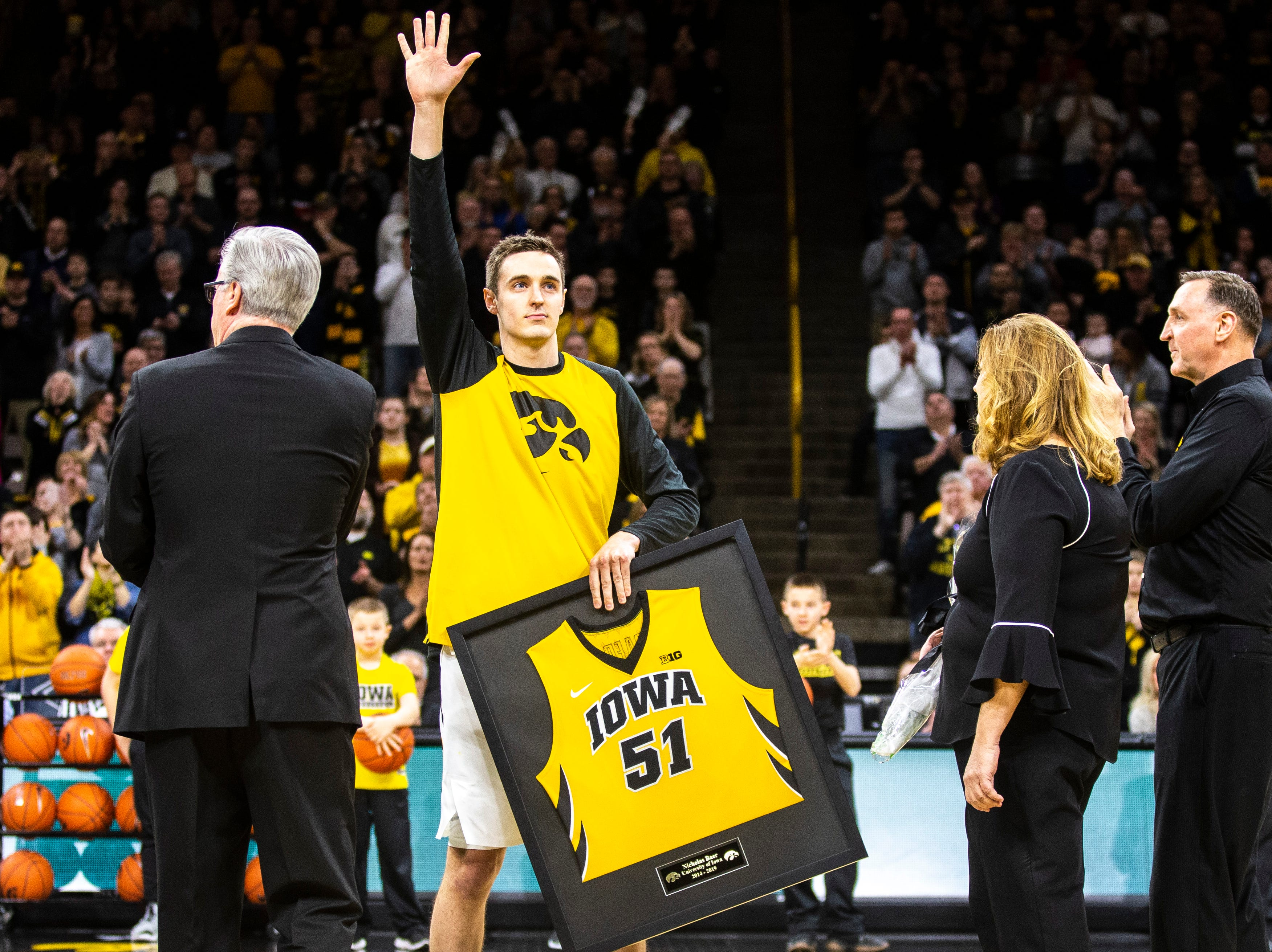 Iowa forward Nicholas Baer (51) waves to fans while holding his framed jersey following senior day activities during a NCAA Big Ten Conference men's basketball game on Saturday, March 2, 2019, at Carver-Hawkeye Arena in Iowa City, Iowa.
