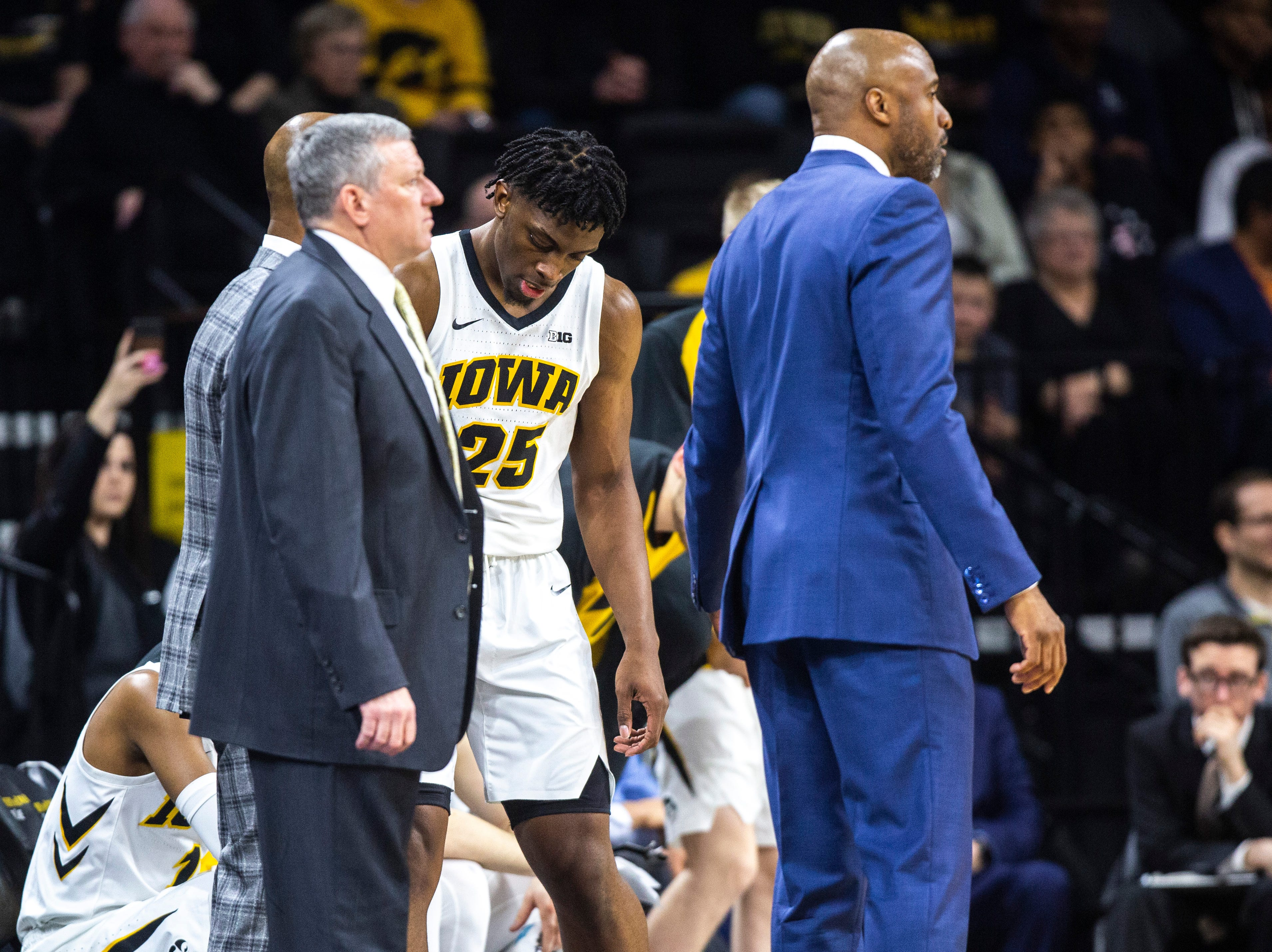 Iowa forward Tyler Cook (25) heads to the bench between Iowa assistant Kirk Speraw and Andrew Francis during a NCAA Big Ten Conference men's basketball game on Saturday, March 2, 2019, at Carver-Hawkeye Arena in Iowa City, Iowa.
