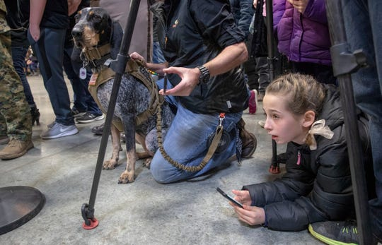 Kyleigh Mathews, 11, Lebanon, lies under a television photographer's tripod as she watches a special retirement ceremony for Brik, the police dog of Boone County Deputy Jacob Pickett, who died in the line of duty a year earlier, 4-H Fairgrounds, Lebanon, Saturday, March 2, 2019.