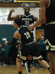 Warren Central Warriors David Bell (22) and Isiah Moore(20) celebrate their win over Lawrence North High School on Friday, Mar 1, 2019. The Warren Central Warriors defeated the Lawrence North Wildcats 27-25.