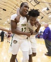 Crispus Attucks junior Jayon Barnett (12), left, and sophomore Donavon Barnett (2) celebrates after winning an IHSAA Class 3A Boys' Basketball Sectional semifinal game at Guerin Catholic High School in Noblesville, Ind., Friday, March 1, 2019. Crispus Attucks won 59-56.