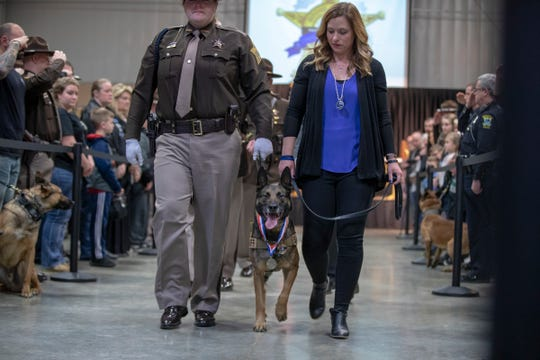 Taylor Nielsen (left), Sheriff's Deputy, and Jennifer Pickett walk Brik as he is retired at an event marking the first anniversary of the shooting of Boone County Deputy Jacob Pickett, which resulted in his death, 4-H Fairgrounds, Lebanon, Saturday, March 2, 2019. Brik was the dog of Jacob Pickett.