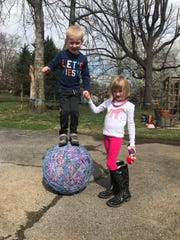 Twins Curtis and Lydia Banks, 6, pose with the family's 30-year-old rubber band ball.