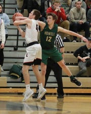 Howell's Tony Honkala reaches out to knock away a shot by Linden's Travis Klocek in a 55-49 district basketball championship game victory at Hartland on Friday, March 1, 2019.