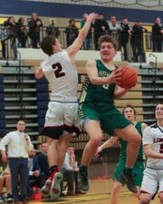 Howell's Josh Palo, who scored 25 points, drives into the lane against Linden's Eli Beil in a 55-49 victory in the district championship game at Hartland on Friday, March 1, 2019.
