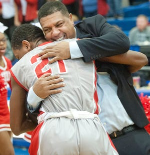 Butler head basketball coach Kentreal Goodin hugs Butler forward DyShawn Brown moments after Butler defeated Bullitt East in the Region 6 championship game, 52-48.