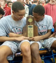 Butler forward Damione Jackson, left, and Butler forward DyShawn Brown, check out the team's championship trophy after Butler defeated Bullitt East in the Region 6 championship game, 52-48.02 March 2019