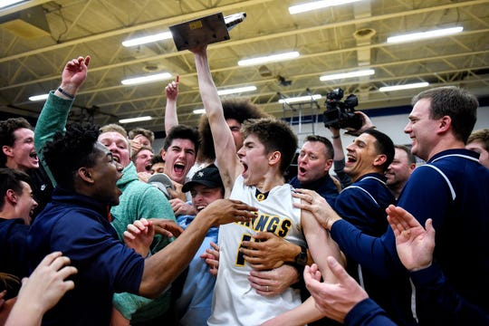 Haslett's Blake Lampman, center, hoists the Division 2 boys basketball championship trophy over his head as the Vikings celebrate their 36-33 victory over Williamston on Friday, March 1, 2019, at Haslett High School.