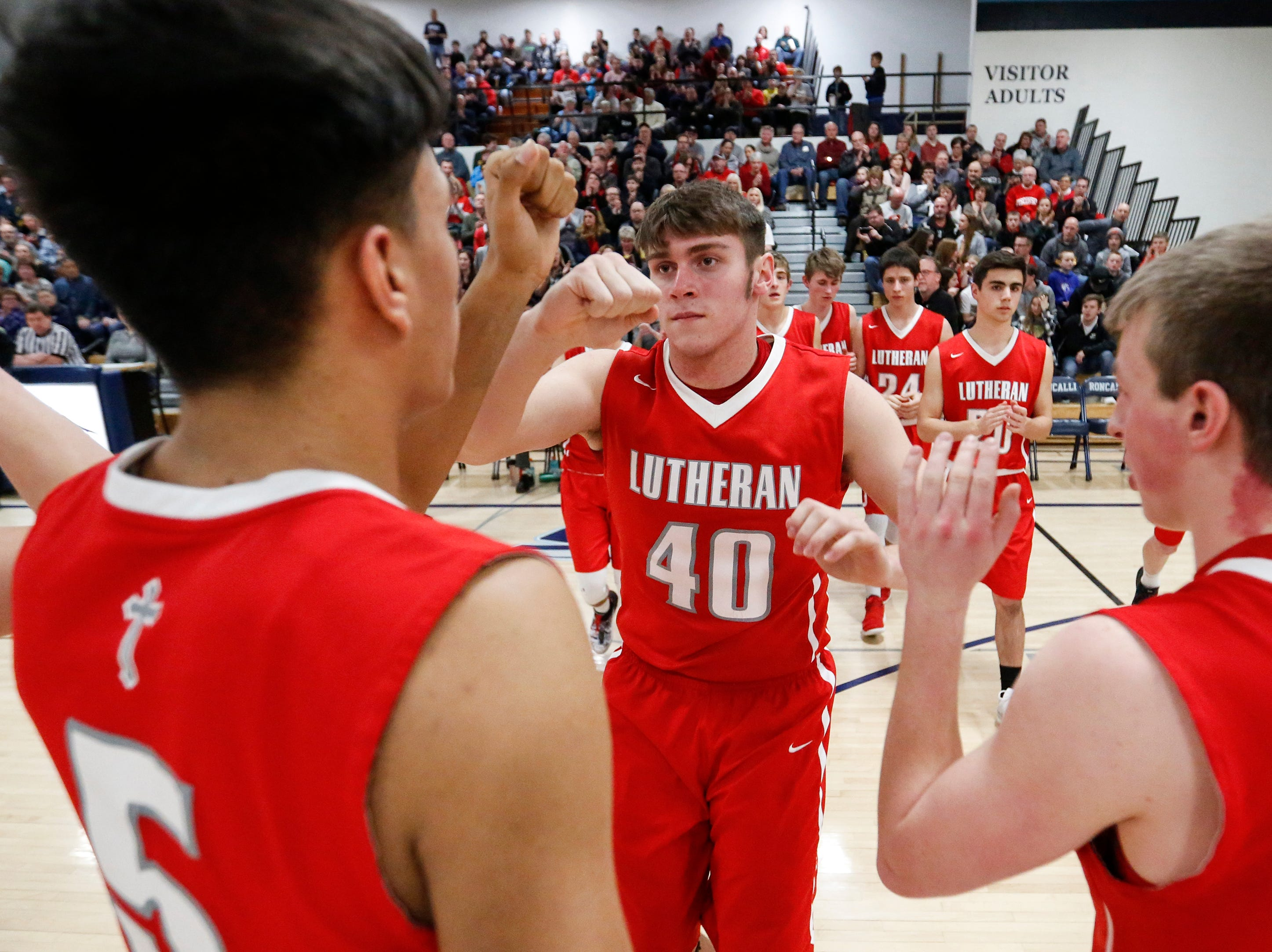 Manitowoc Lutheran's Korey Garceau fist bumps his teammates as he's introduced before a WIAA Division 4 regional semifinal game against Roncalli at Roncalli High School Friday, March 1, 2019, in Manitowoc, Wis. Joshua Clark/USA TODAY NETWORK-Wisconsin