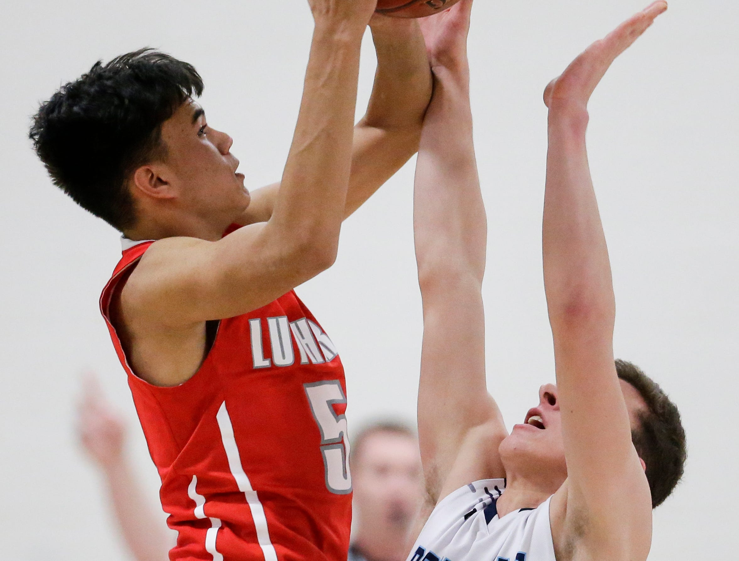 Manitowoc Lutheran's Santana Lomibao (5) puts up a shot over Roncalli's Daniel Burgarino (1) during a WIAA Division 4 regional semifinal game at Roncalli High School Friday, March 1, 2019, in Manitowoc, Wis. Joshua Clark/USA TODAY NETWORK-Wisconsin