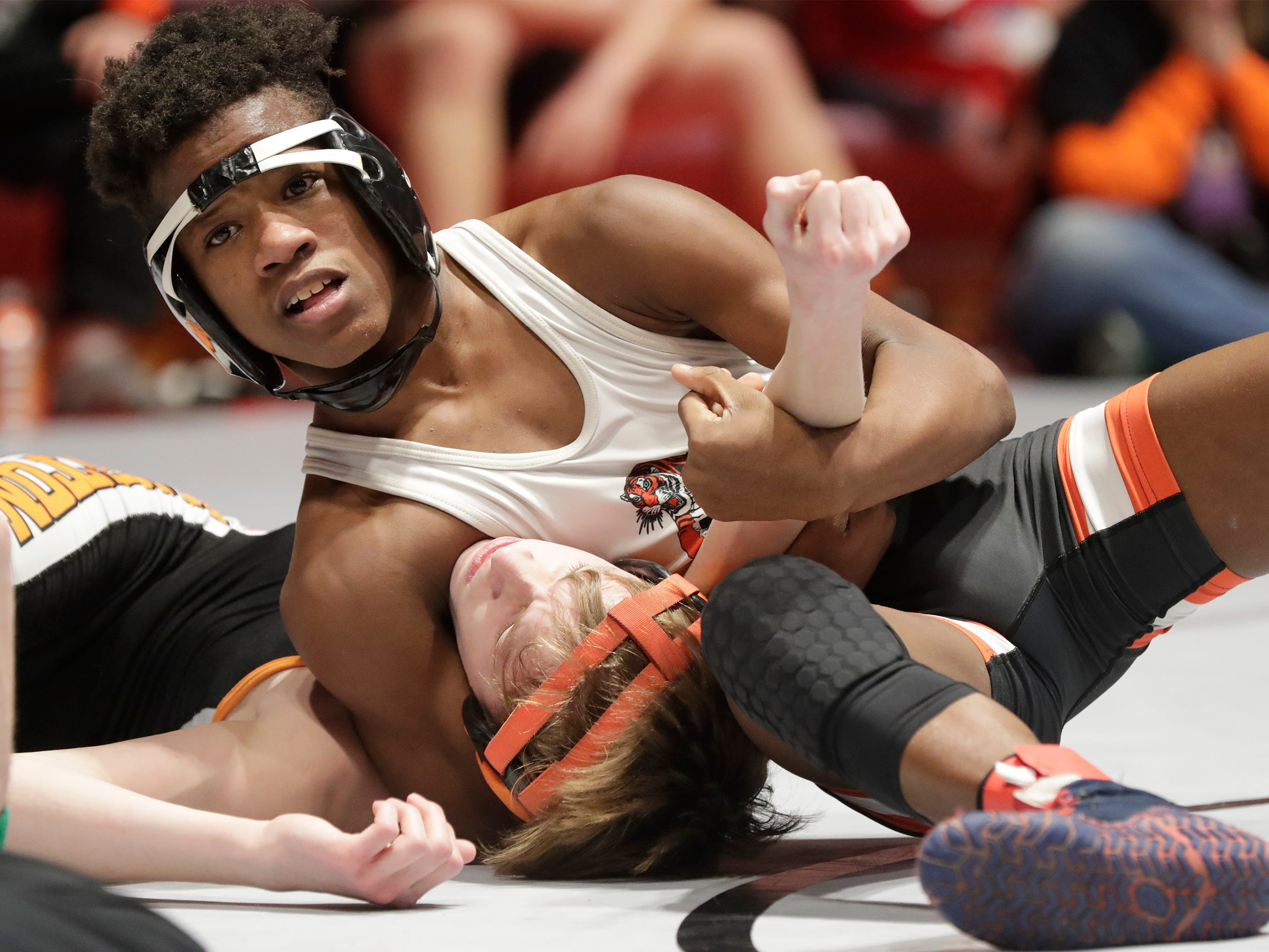 Siriuis Conrad, top, works to keep Burlington's Ty Kiesler down during a 106-pound match, Friday, March 1, 2019, in Madison, Wis.
