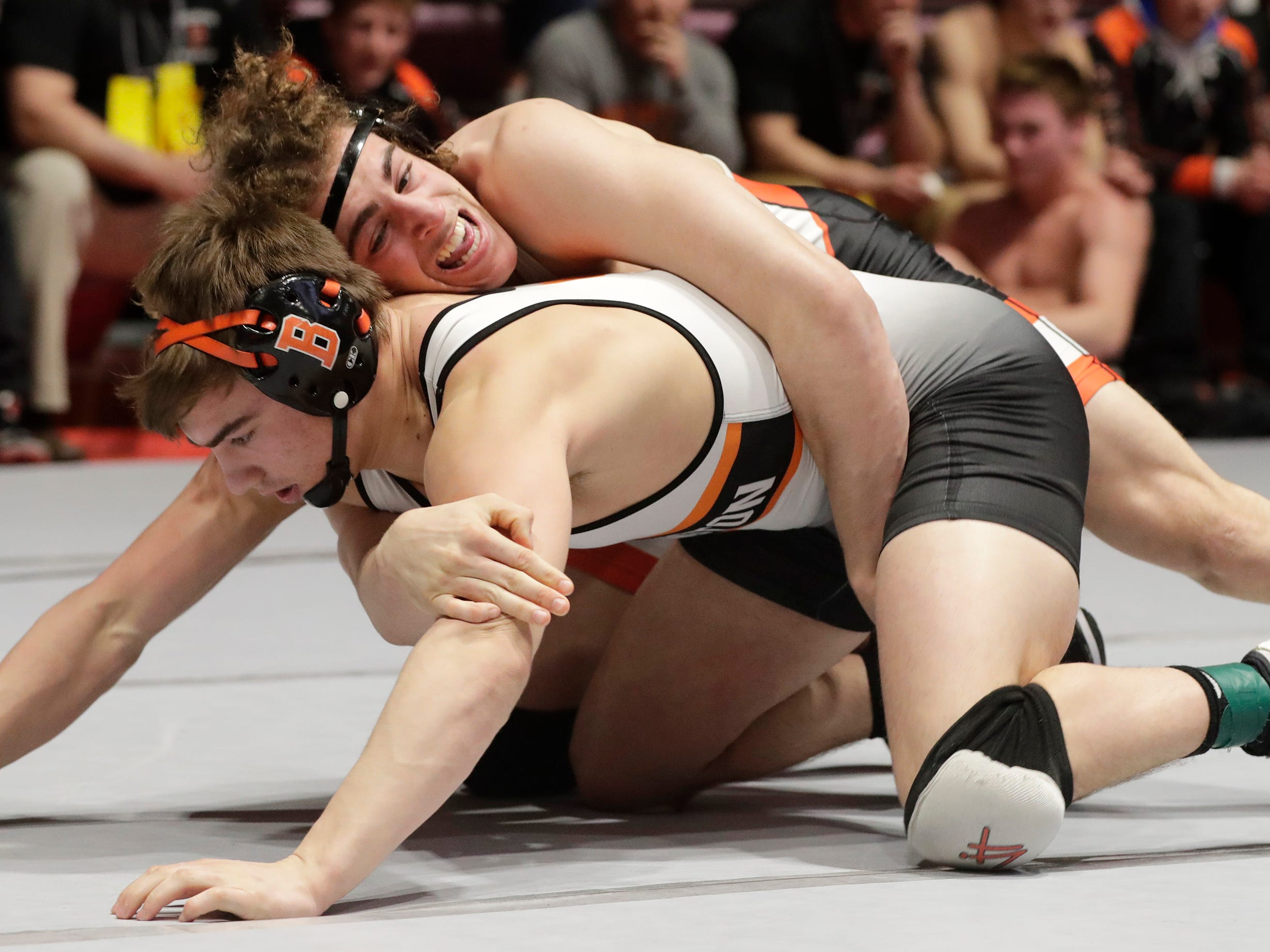Bentley Schwanebeck-Ostermann, top, wrestles Burlington's Zach Wallace in a 182-pound match, Friday, March 1, 2019, in Madison, Wis.