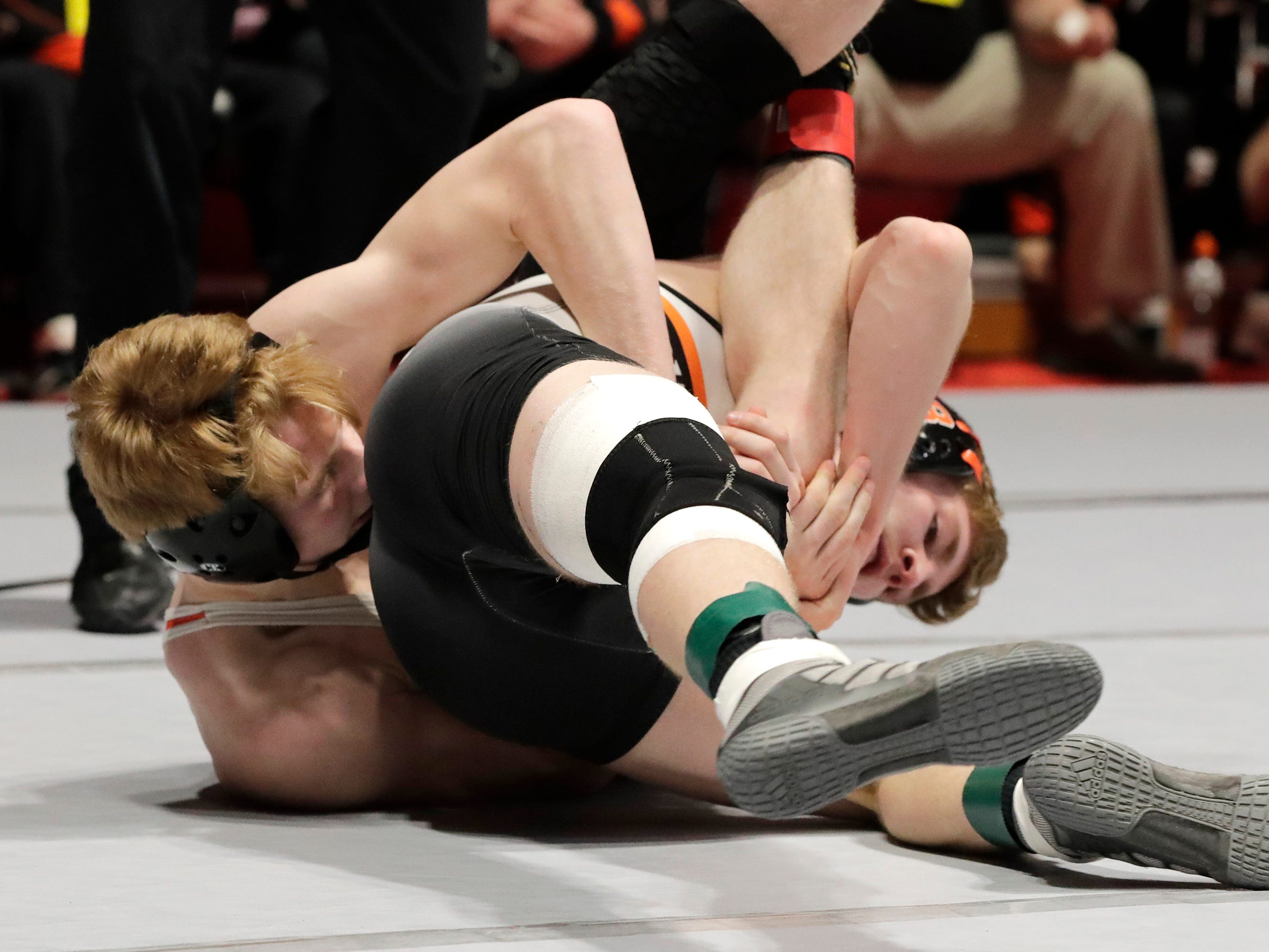 Burlington's Ryan Dolezal, right, wrestles Marshfield's Zach Weiler, left, in a 132-pound match, Friday, March 1, 2019, in Madison, Wis.