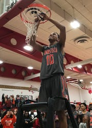 Cam Todd takes his turn cutting down the net after his free throw heroics helped Mansfield Senior win a Division II sectional championship.