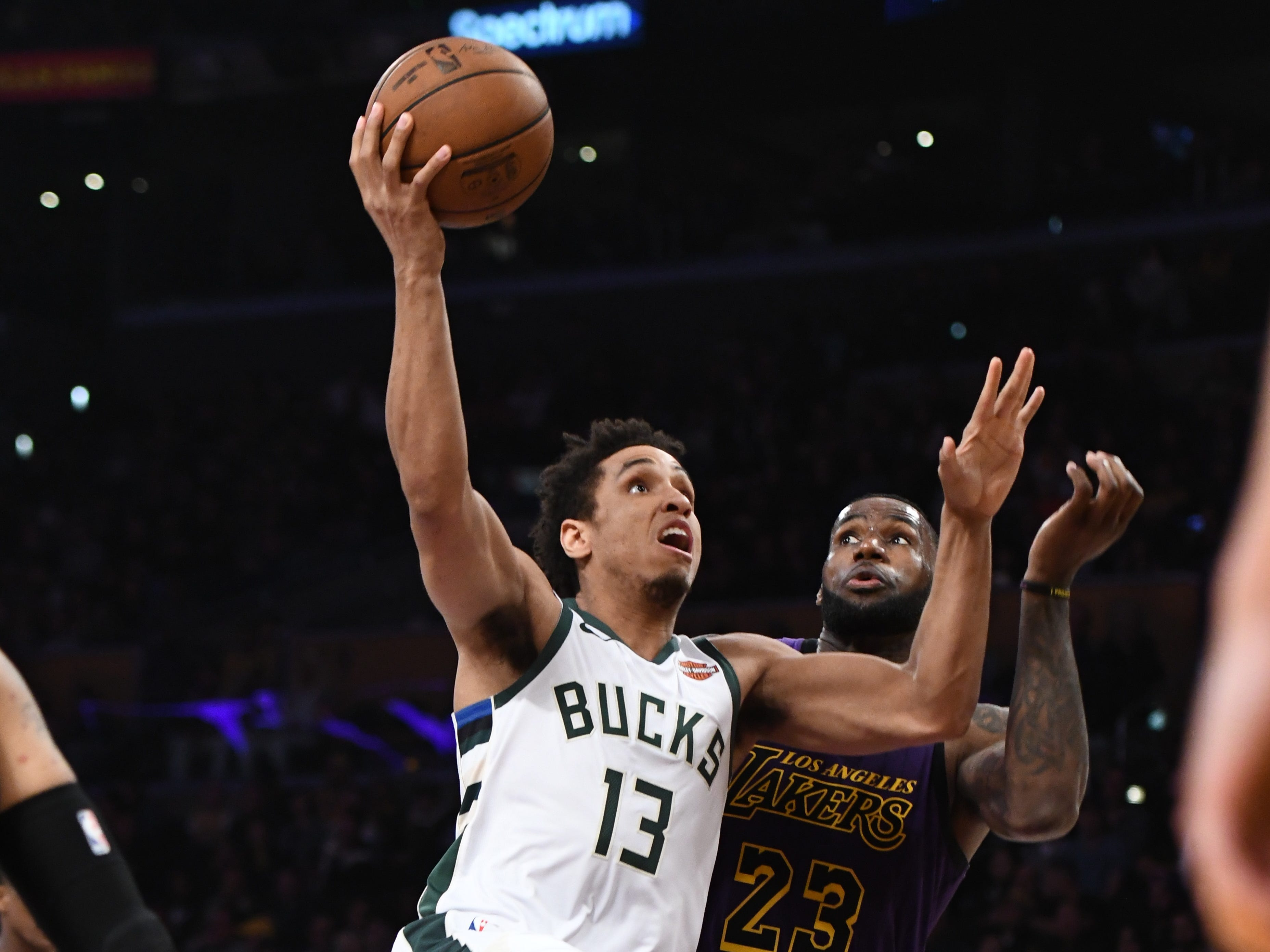 Bucks guard Malcolm Brogdon beats LeBron James of the Lakers to the basket for a layup during the second half.