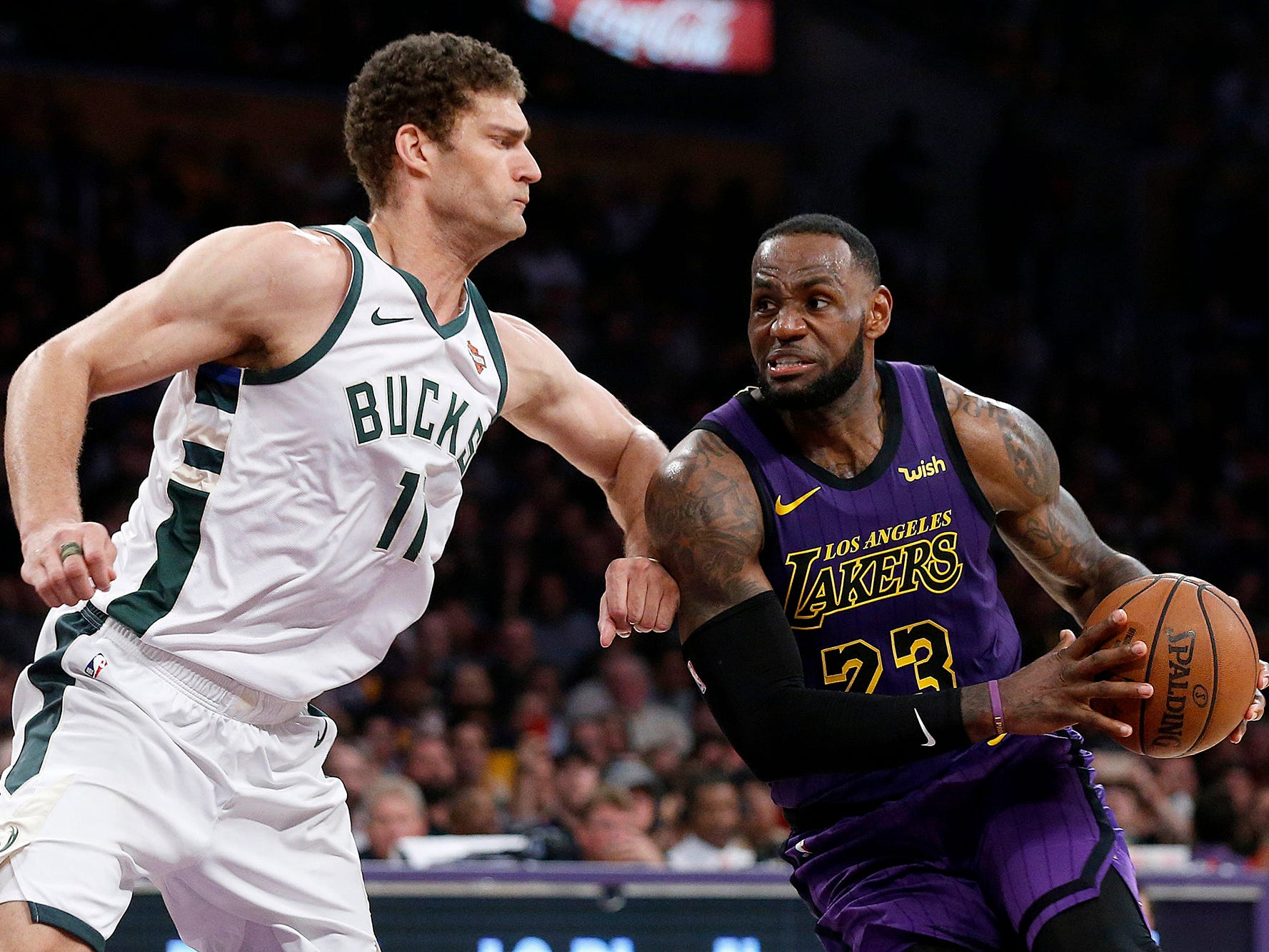 In a battle of serious expressions, Bucks center Brook Lopez tries to repel LeBron James' drive to the basket in the second half.