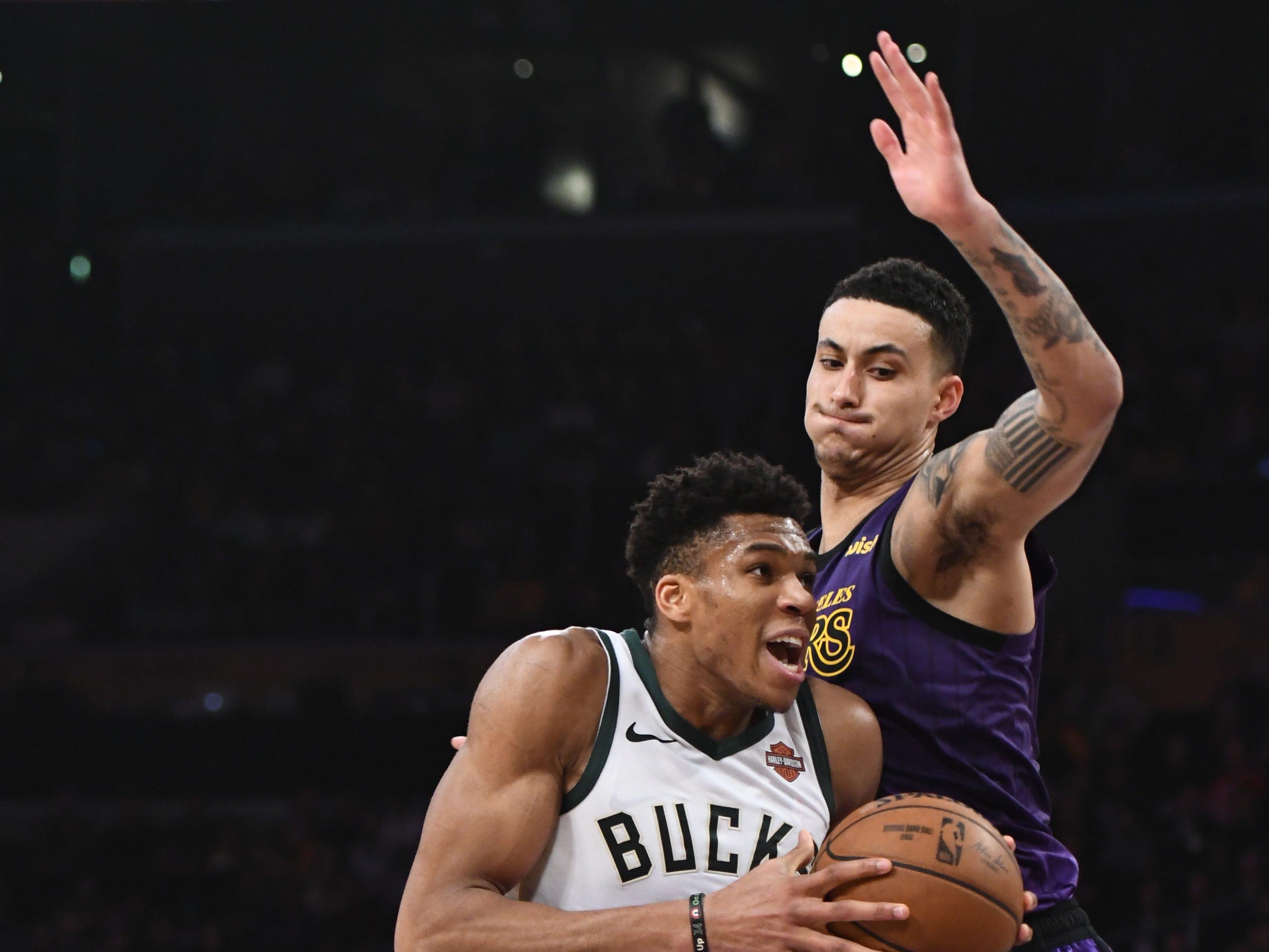 Bucks forward Giannis Antetokounmpo drivers to the basket against the tight defense of Lakers forward Kyle Kuzma during the third quarter.