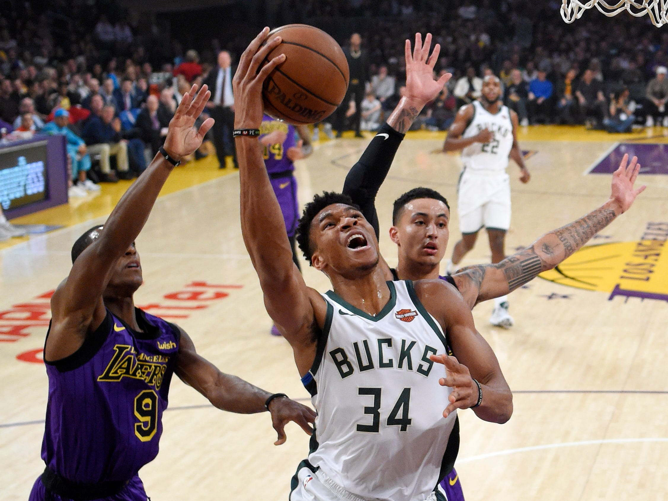 Bucks forward Giannis Antetokounmpo gets past Rajon Rondo (left) and Kyle Kuzma of the Lakers for a basket during the first half.