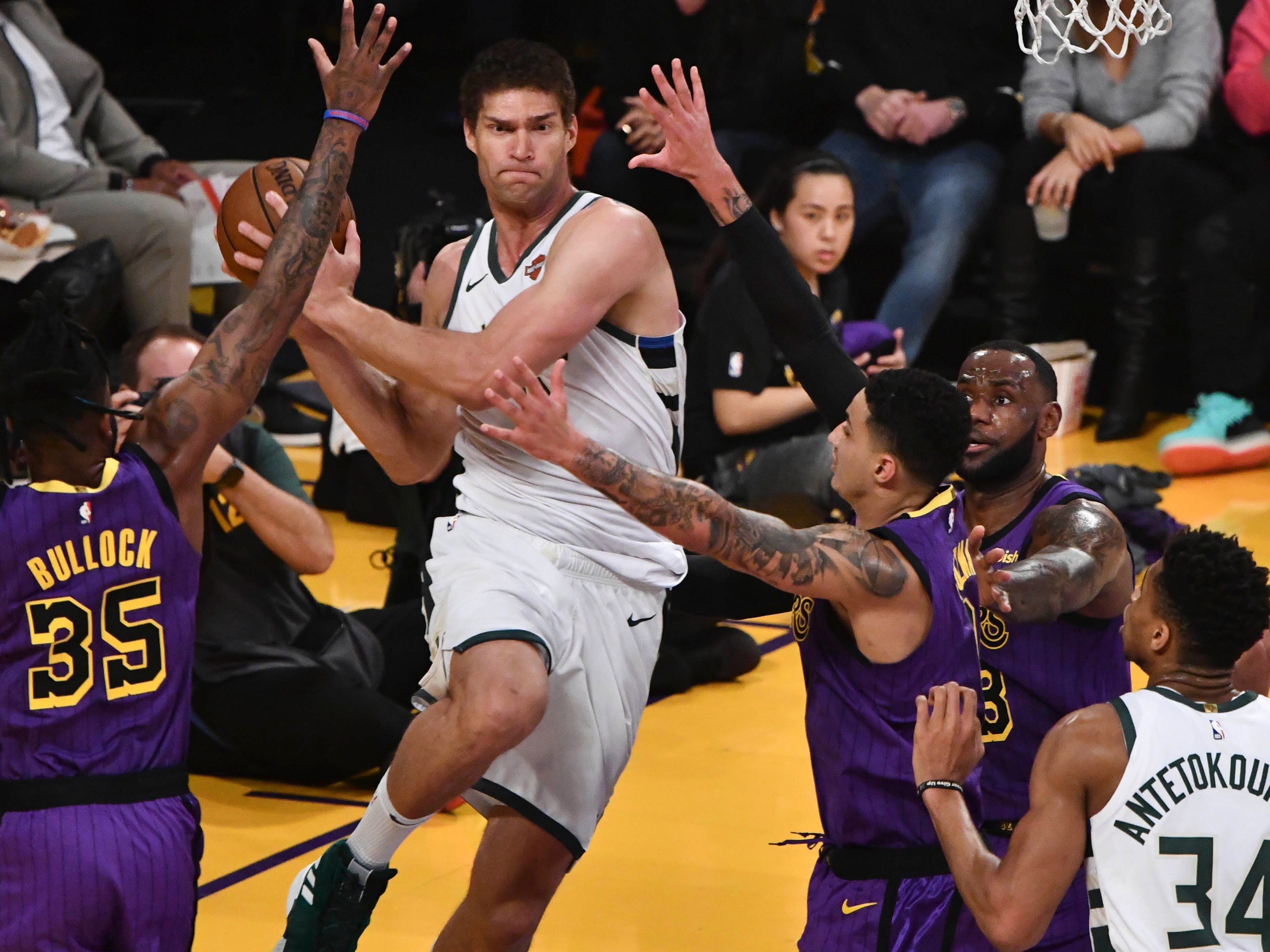 Bucks center Brook Lopez goes airborne as he looks for a teammate to pass to after getting pinned along the baseline by a trio of Lakers during the first quarter.