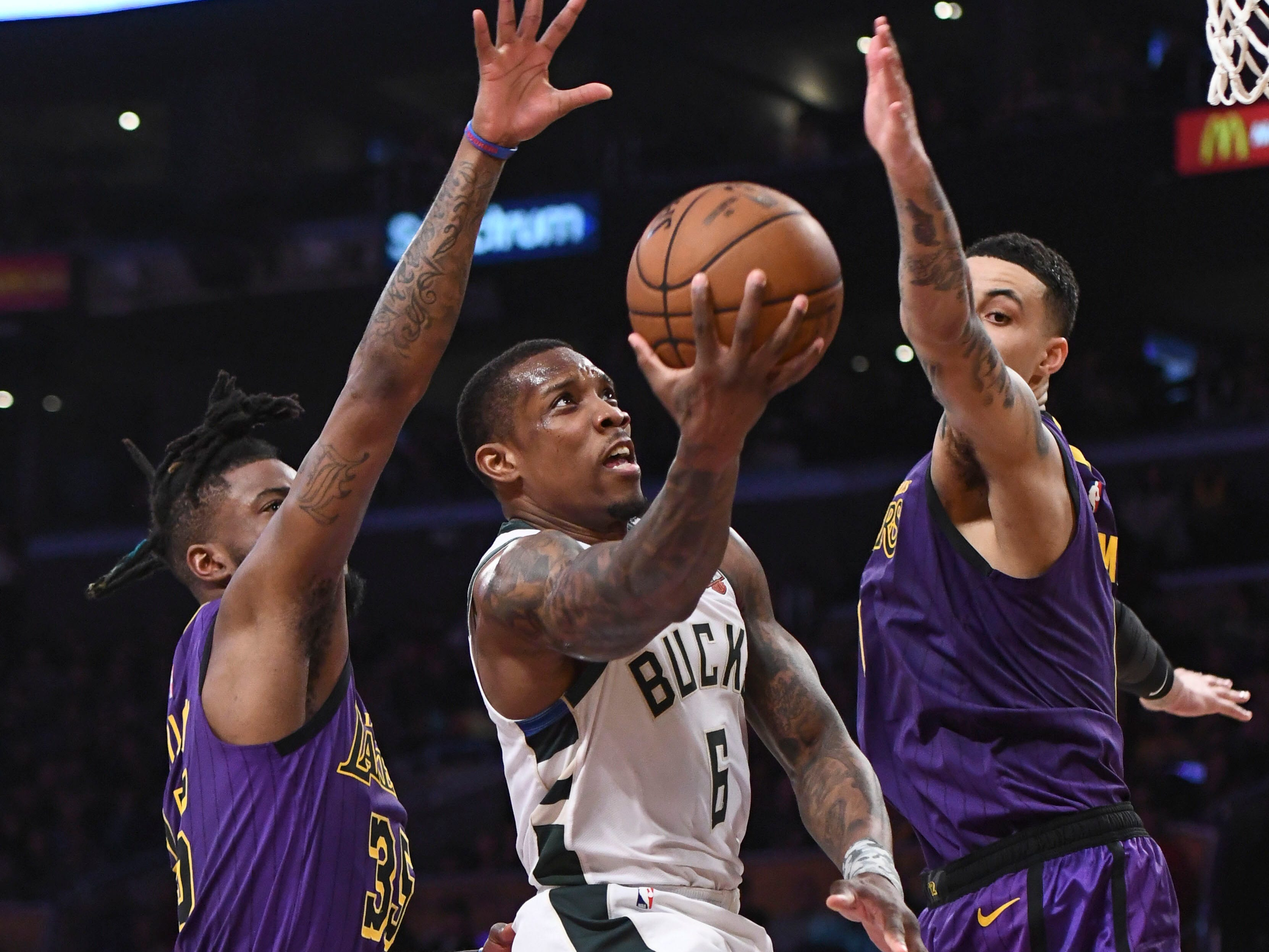Bucks guard Eric Bledsoe slices between Reggie Bullock (left) and Kyle Kuzma of the Lakers for a basket during the second half.