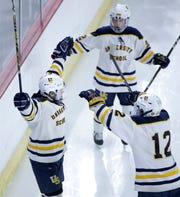 Teammates join Tyler Herzberg, left, in celebration of a goal in a state semifinal last season.