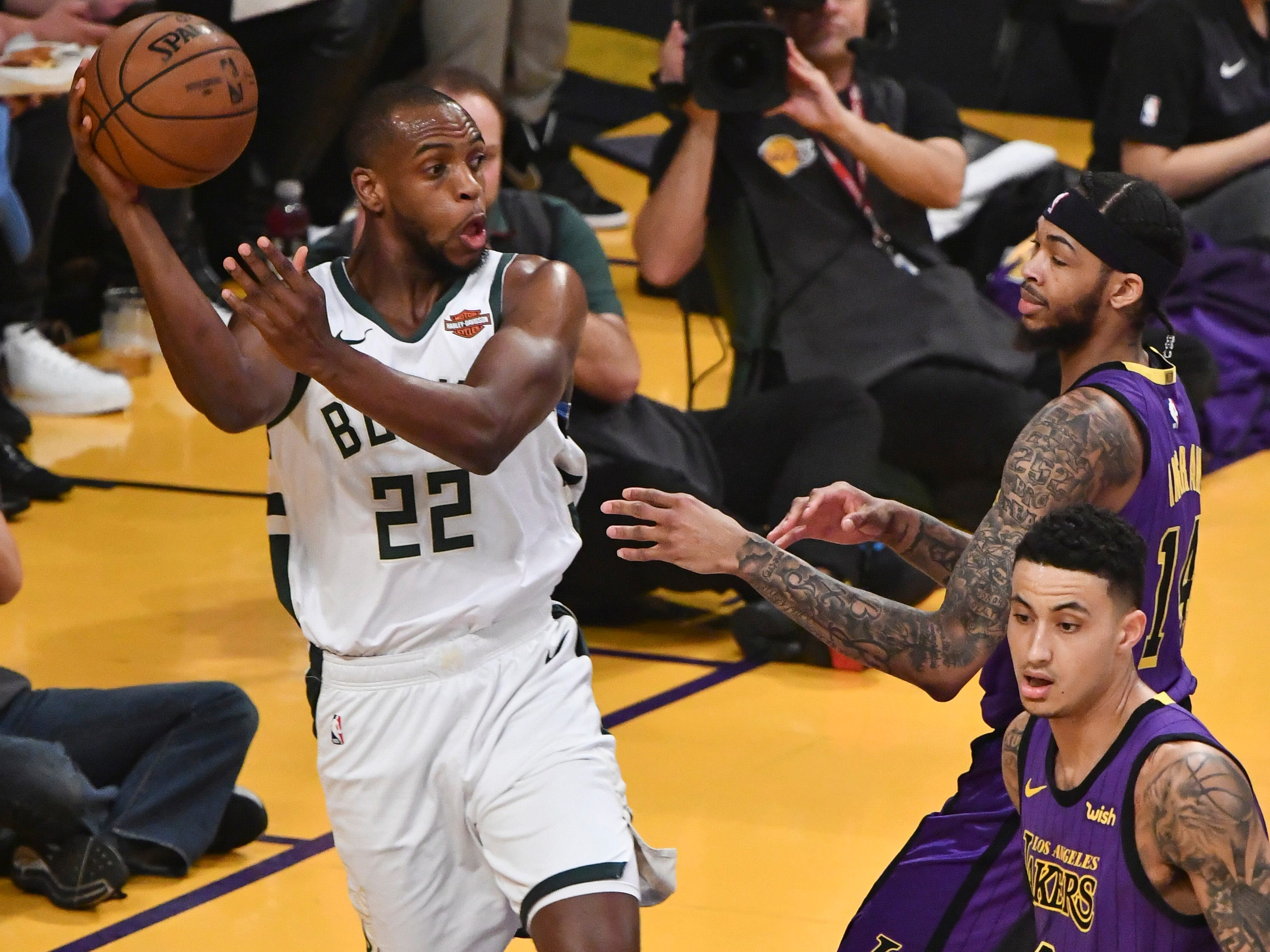 Bucks forward Khris Middleton gets ready to kick a pass out to a teammate after grabbing a rebound for the Lakers' Brandon Ingram got to it during the first quarter.