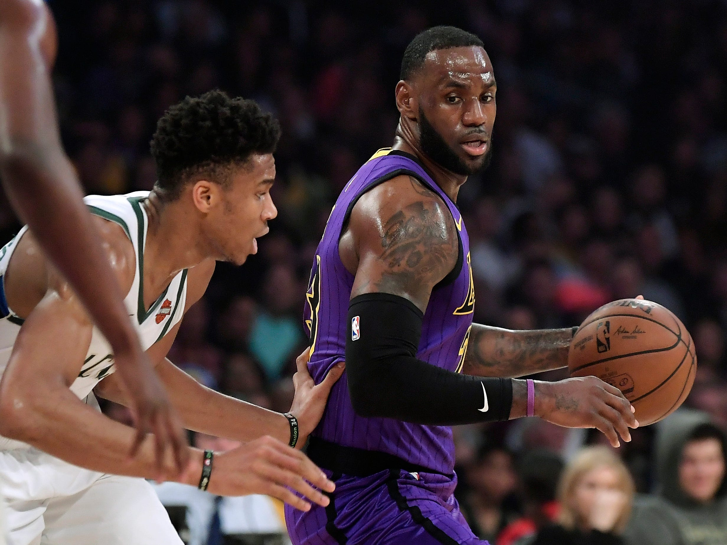 Bucks forward Giannis Antetokounmpo gets ready for Lakers forward LeBron James to make his move during the first half.