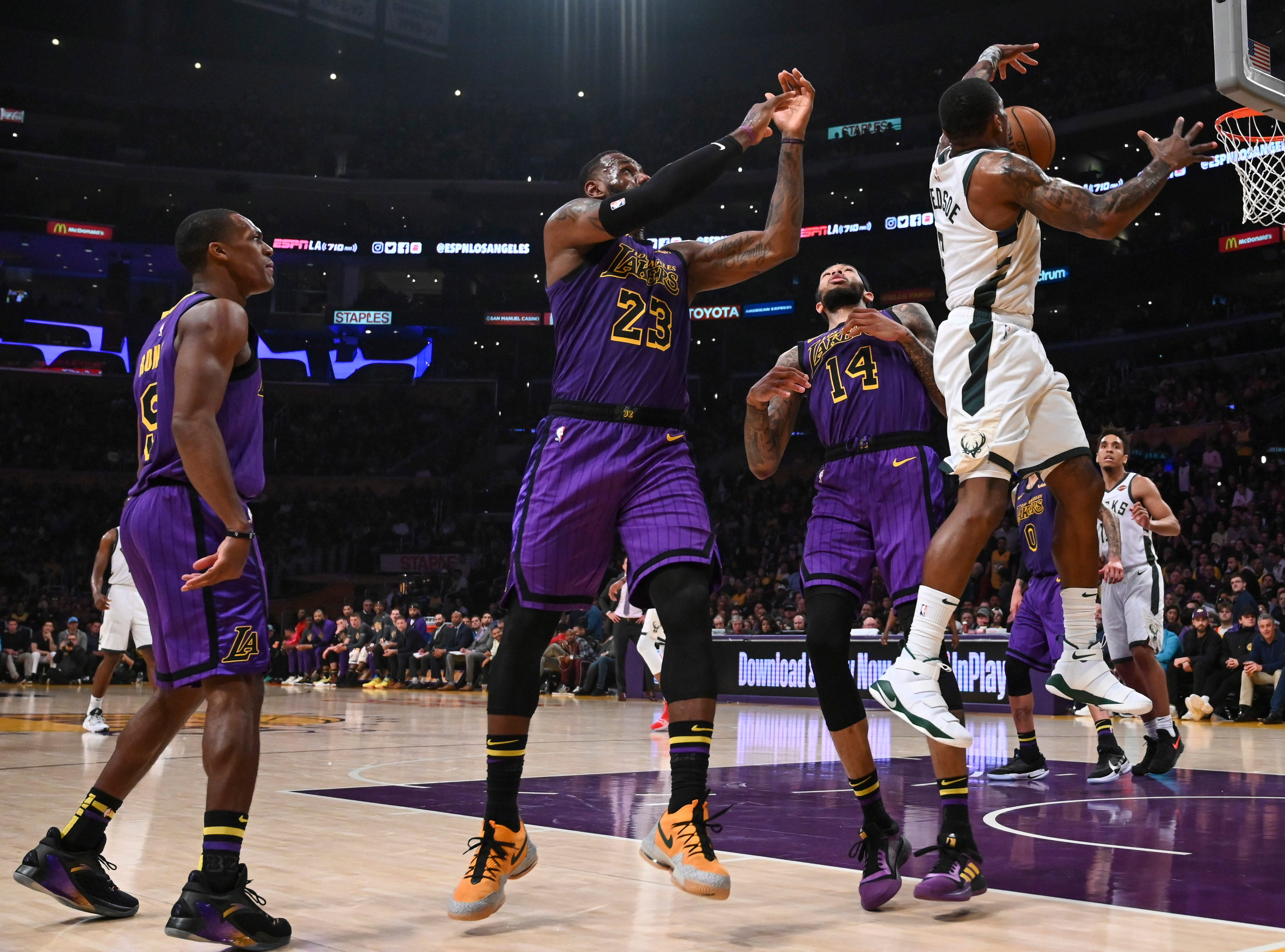 Bucks guard Eric Bledsoe gets behind a trio of Lakers, including LeBron James (23) and Brandon Ingram (14), for a key rebound during the second half.