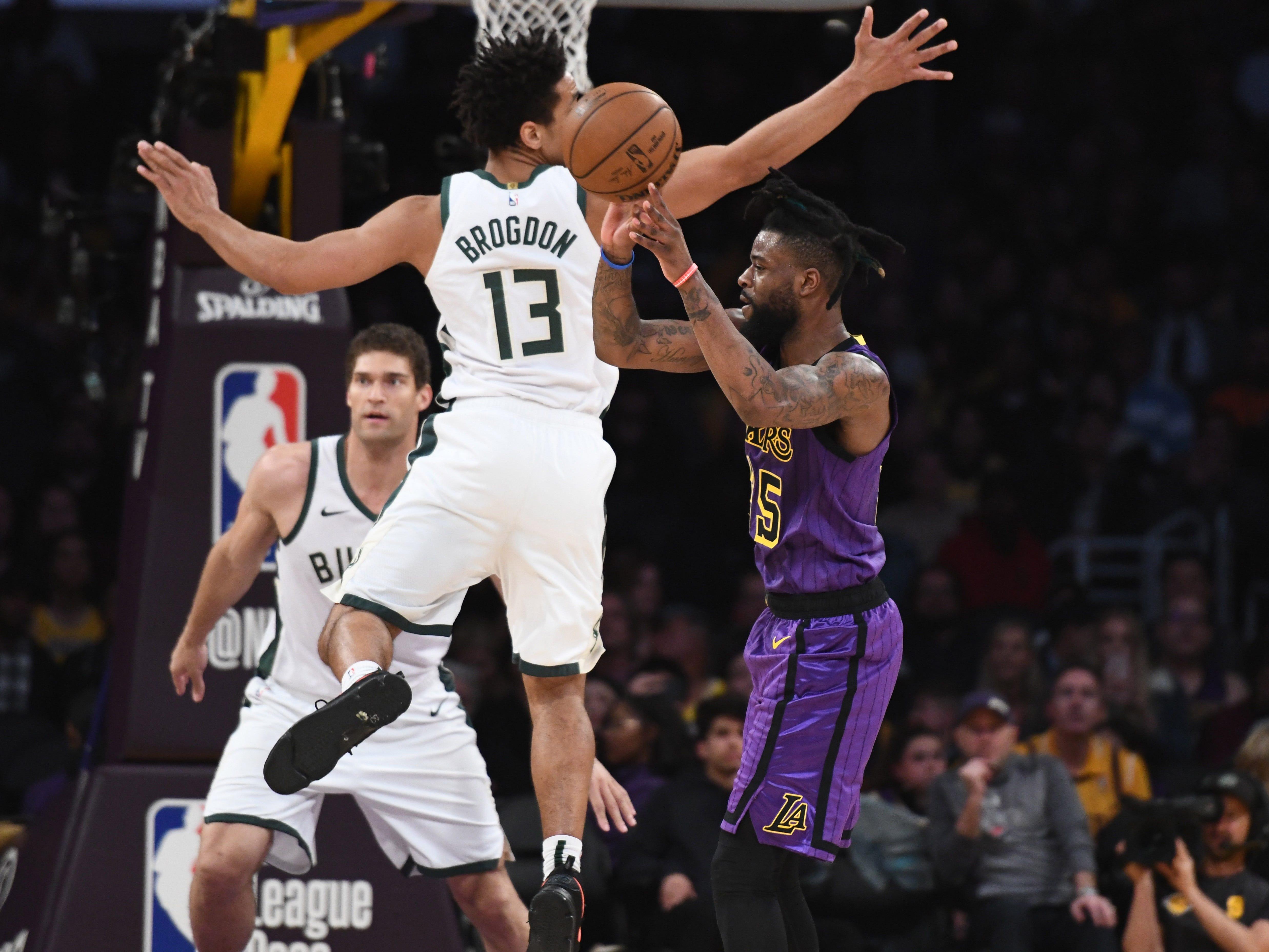 Lakers guard Reggie Bullock passes the ball as Bucks guard Malcolm Brogdon goes flying past himem during the fourth quarter.