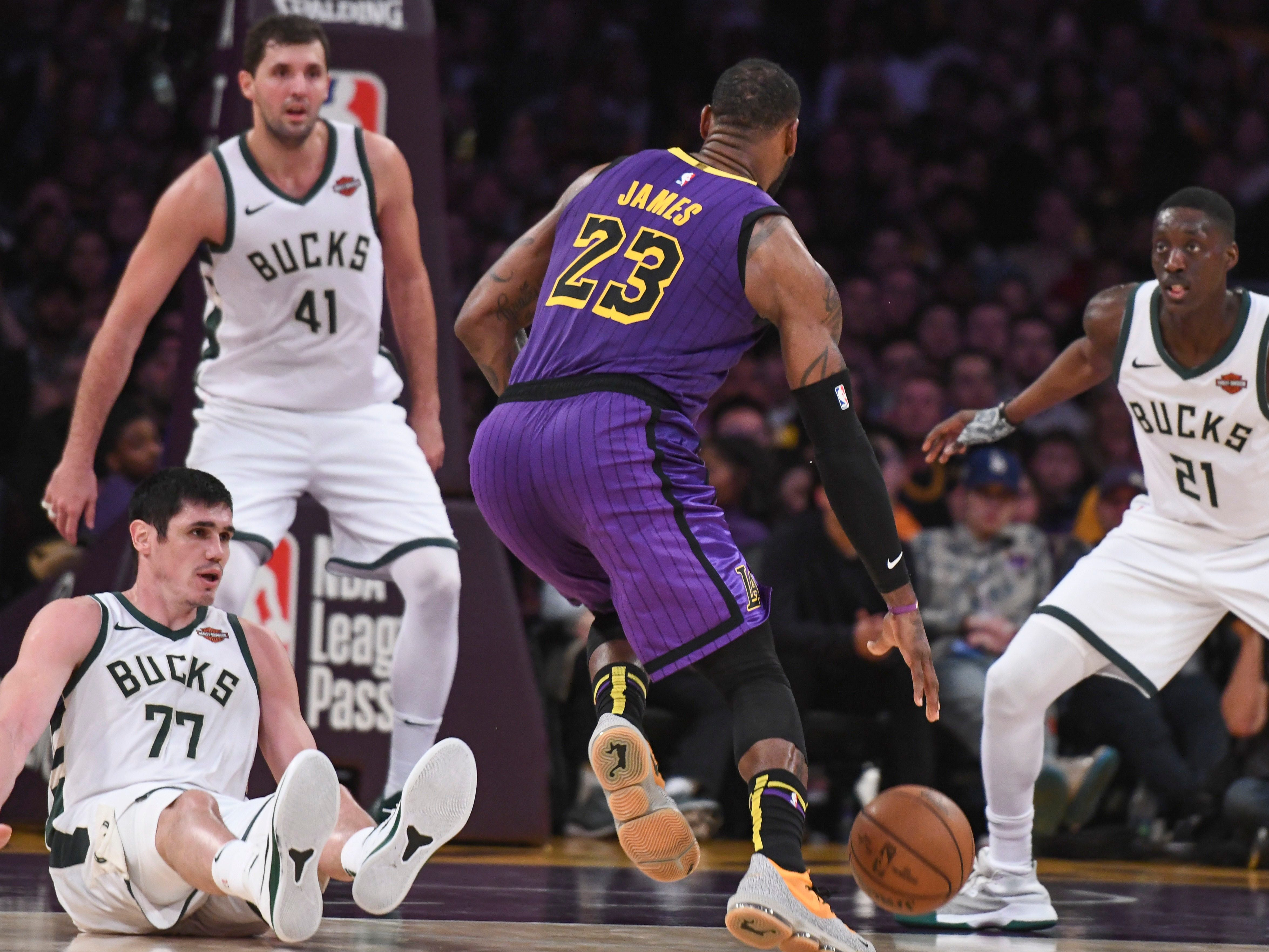 Lakers forward LeBron James sends Ersan Ilyasova of the Bucks to the floor as he drives to the rack during the second half.