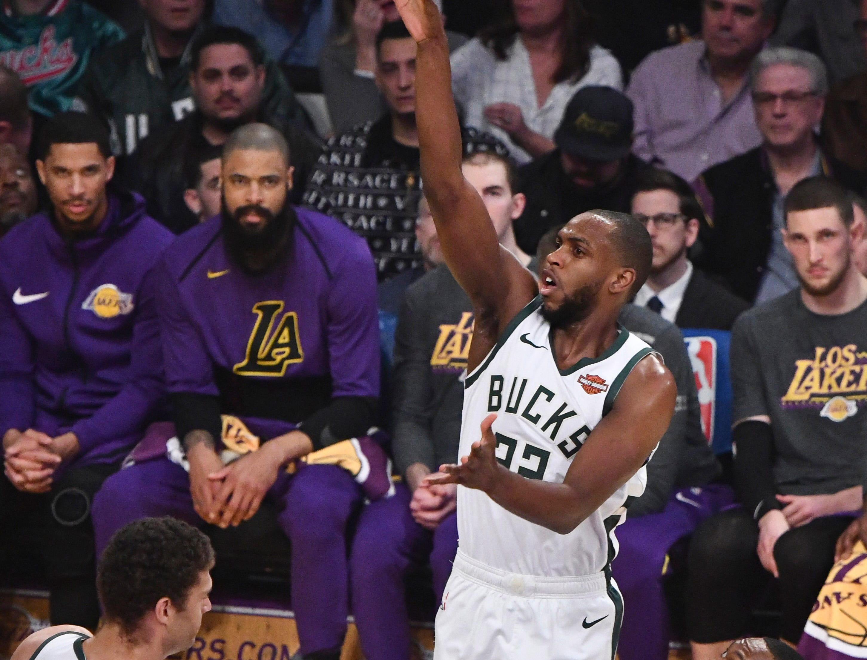 Bucks forward Khris Middleton shoots as Lakers guard Rajon Rondo tries to avoid fouling him during the first quarter.