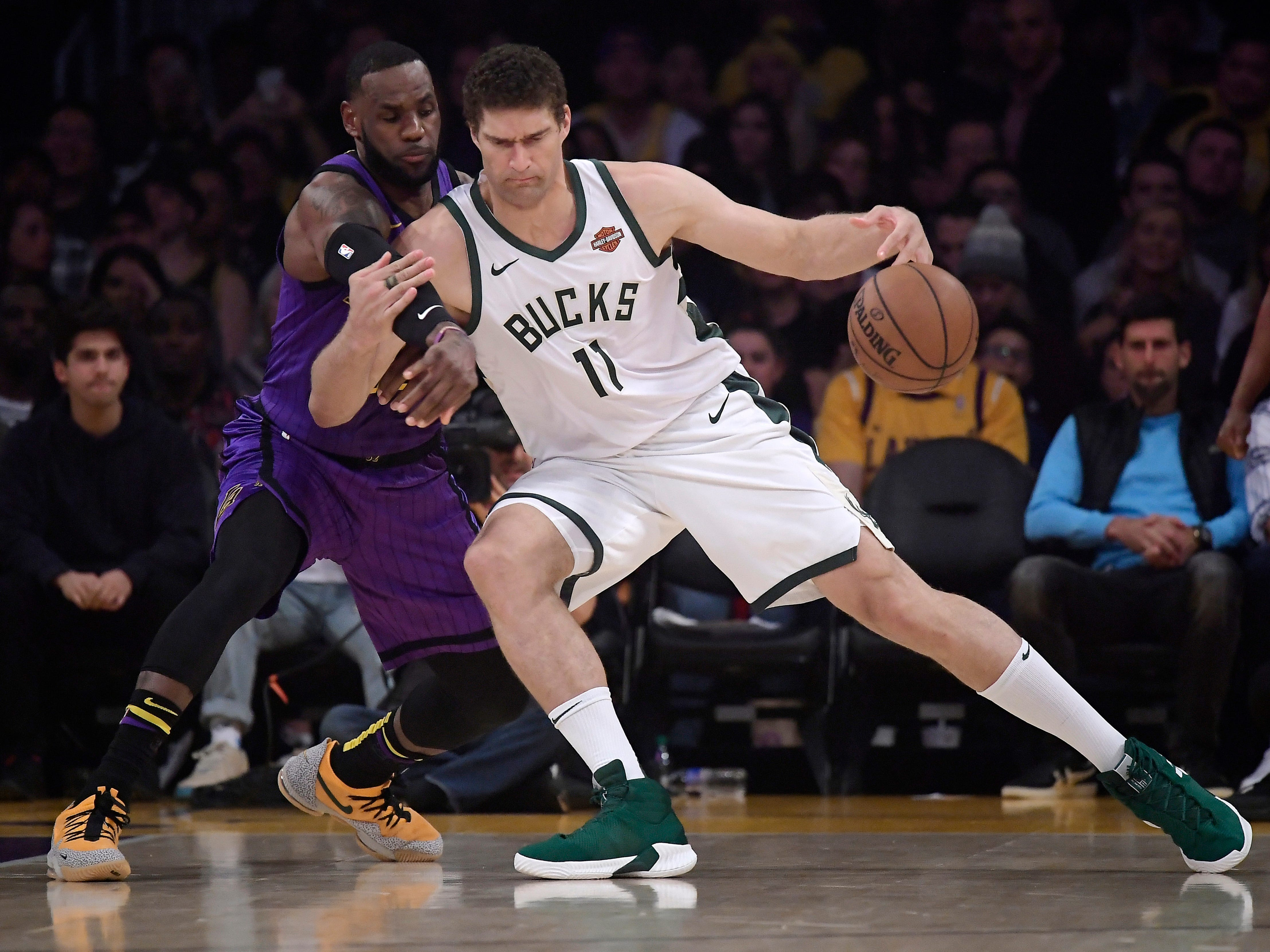 Bucks center Brook Lopez jostles with Lakers forward LeBron James as he tries to work his way to the basket Friday night.