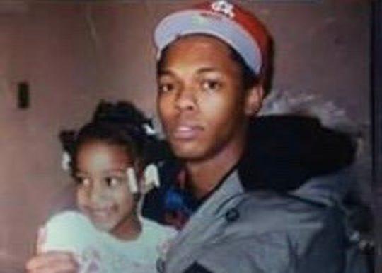 Quincy Reid holding his goddaughter.