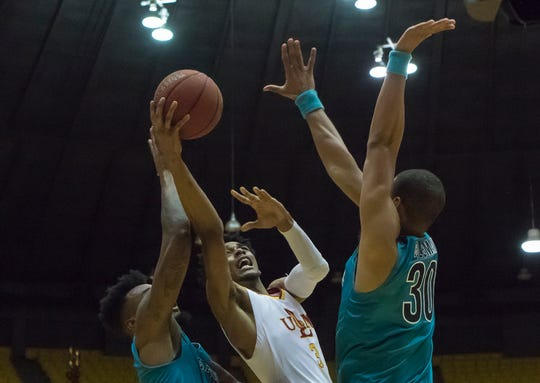 University of Louisiana at Monroe's JD Williams (3) stretches the ball towards the net while Coastal Carolina's Ajay Sanders (4) and Josh Coleman (30) attempt to defend during the game at Fant-Ewing Coliseum in Monroe, La. on March 2.