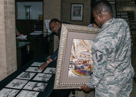 MSgt. Columbus Cook, right, brings in an illustration he did for a historic Mobile hotel. Cook donated several pieces of his artwork to Wetumpka on Friday, Feb. 22, 2019.