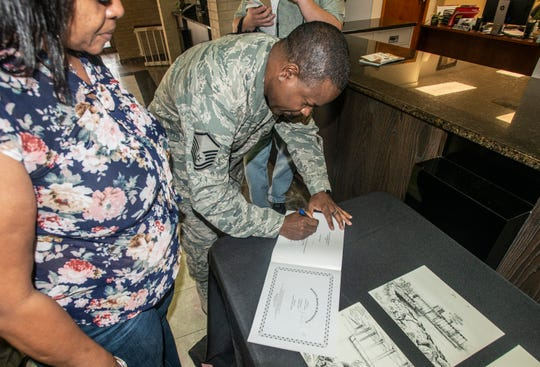 """MSgt. Columbus Cook signs a copy of """"Marty Makes a Difference,"""" a book he illustrated. Cook donated several pieces of his artwork to Wetumpka on Friday, Feb. 22, 2019."""