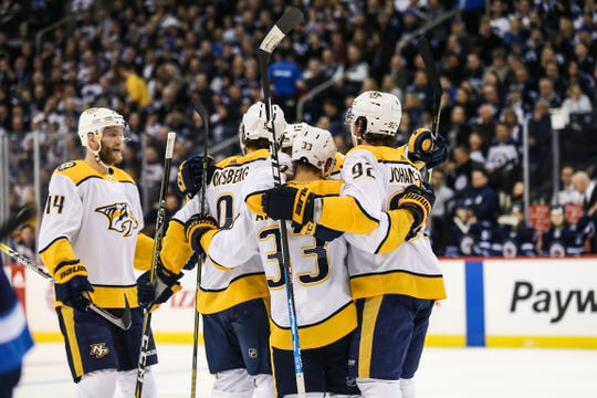 Predators forward Viktor Arvidsson (33) celebrates with teammates after scoring a goal against the Jets during the first period March 1.