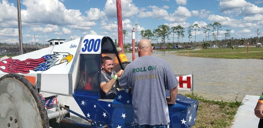 Tyler Johns, in his pro-modified swamp buggy Patriot, gets congratulated by fellow driver Dan Greeling (right) after running the fastest lap of the day Saturday at the practice session for the Swamp Buggy Races Bud Cup Championship at Florida Sports Park.