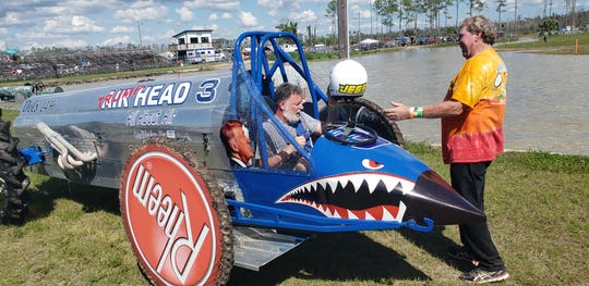Reece Gardner, seated in his pro-modified swamp buggy Trump Head, talks with fellow driver Bobby Williams during a practice session Saturday at Florida Sports Park. Gardner, a supporter of President Trump, changed the name of his buggy, formerly called Air Head, after he said he got in trouble from swamp buggy organizers for making jokes about a border wall on the microphone at the last races.