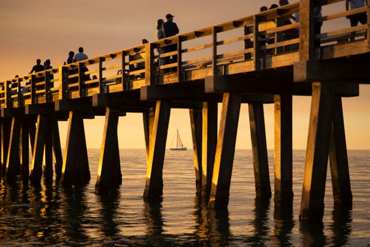 A boat sails near Naples Pier during sunset on Thursday, February 7, 2019.