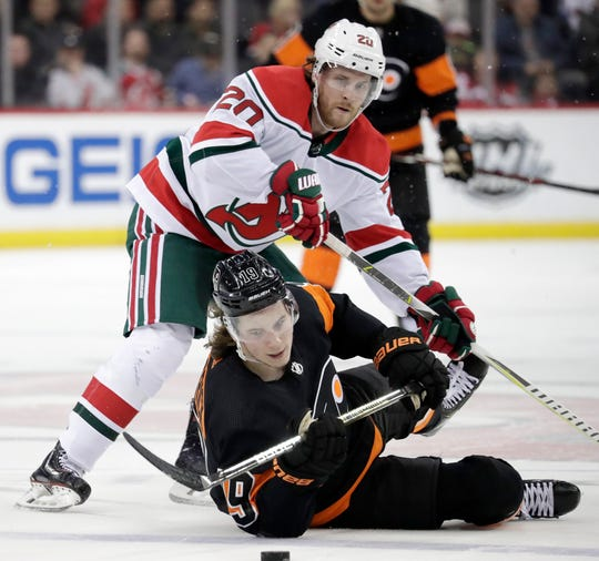 New Jersey Devils center Blake Coleman (20) and Philadelphia Flyers center Nolan Patrick (19) compete for the puck during the first period of an NHL hockey game Friday, March 1, 2019, in Newark, N.J.