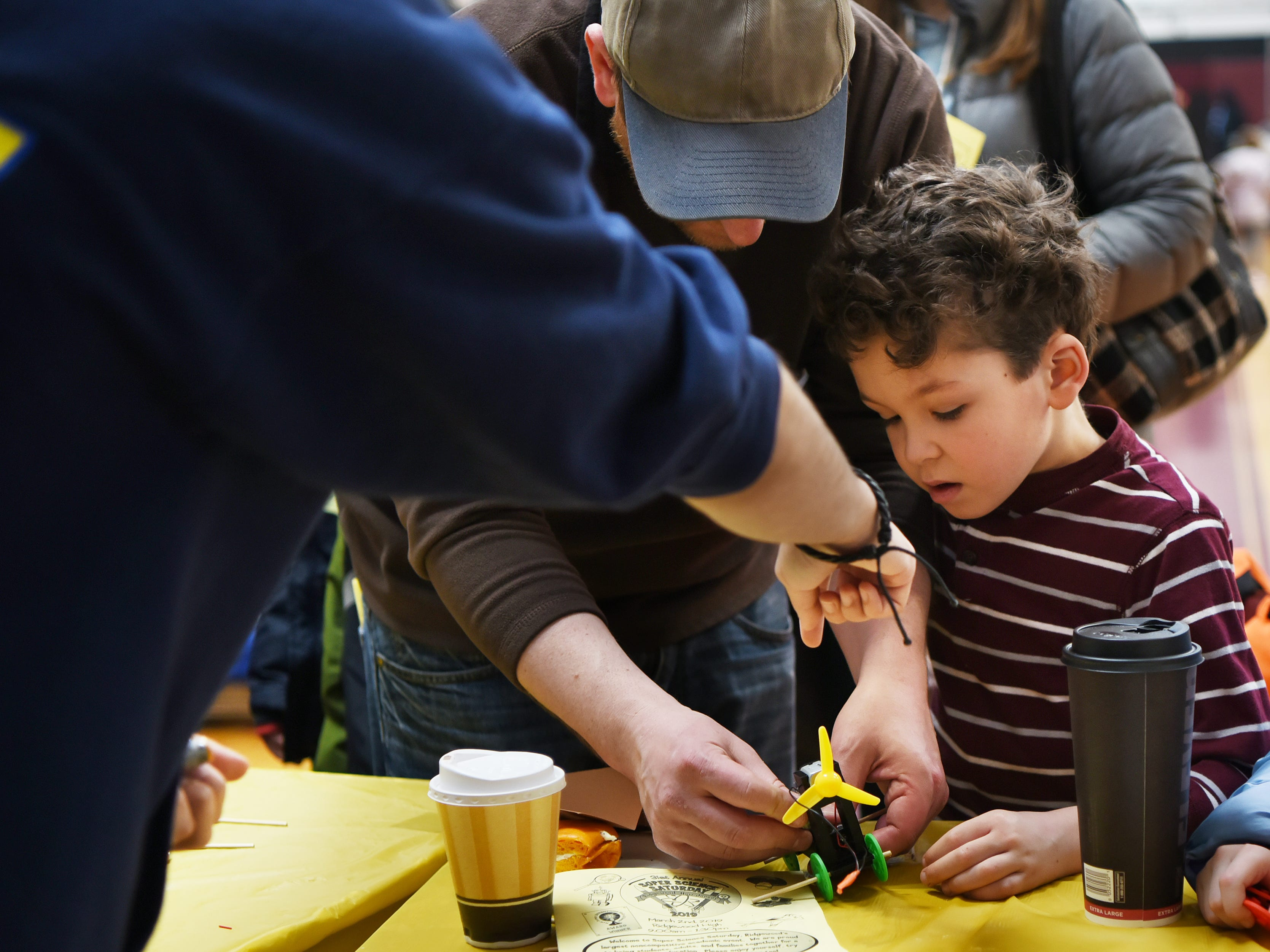 Jason Muzio, 7, creates a wind-powered electric car with some assistance. This is one of many activities during Super Science Saturday held at Ridgewood High School in Ridgewood on Saturday March 2, 2019.