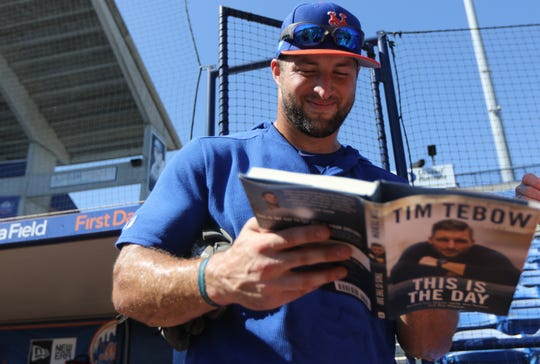 Tim Tebow signs a copy of his book for a fan, Saturday, March 2, 2019.