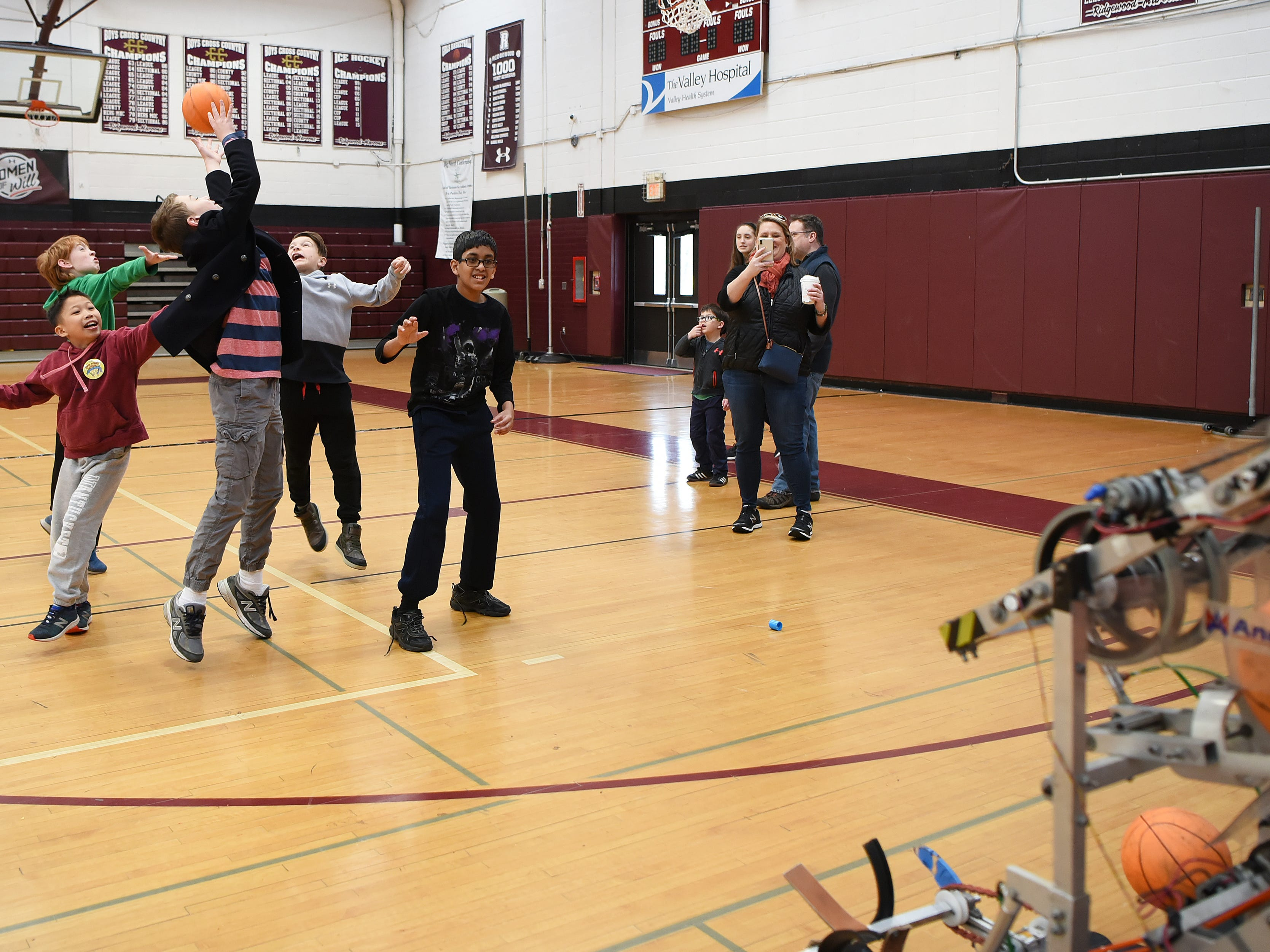 A group of boys all try to catch a basketball being launched by a robot. This is one of many activities during Super Science Saturday held at Ridgewood High School in Ridgewood on Saturday March 2, 2019.