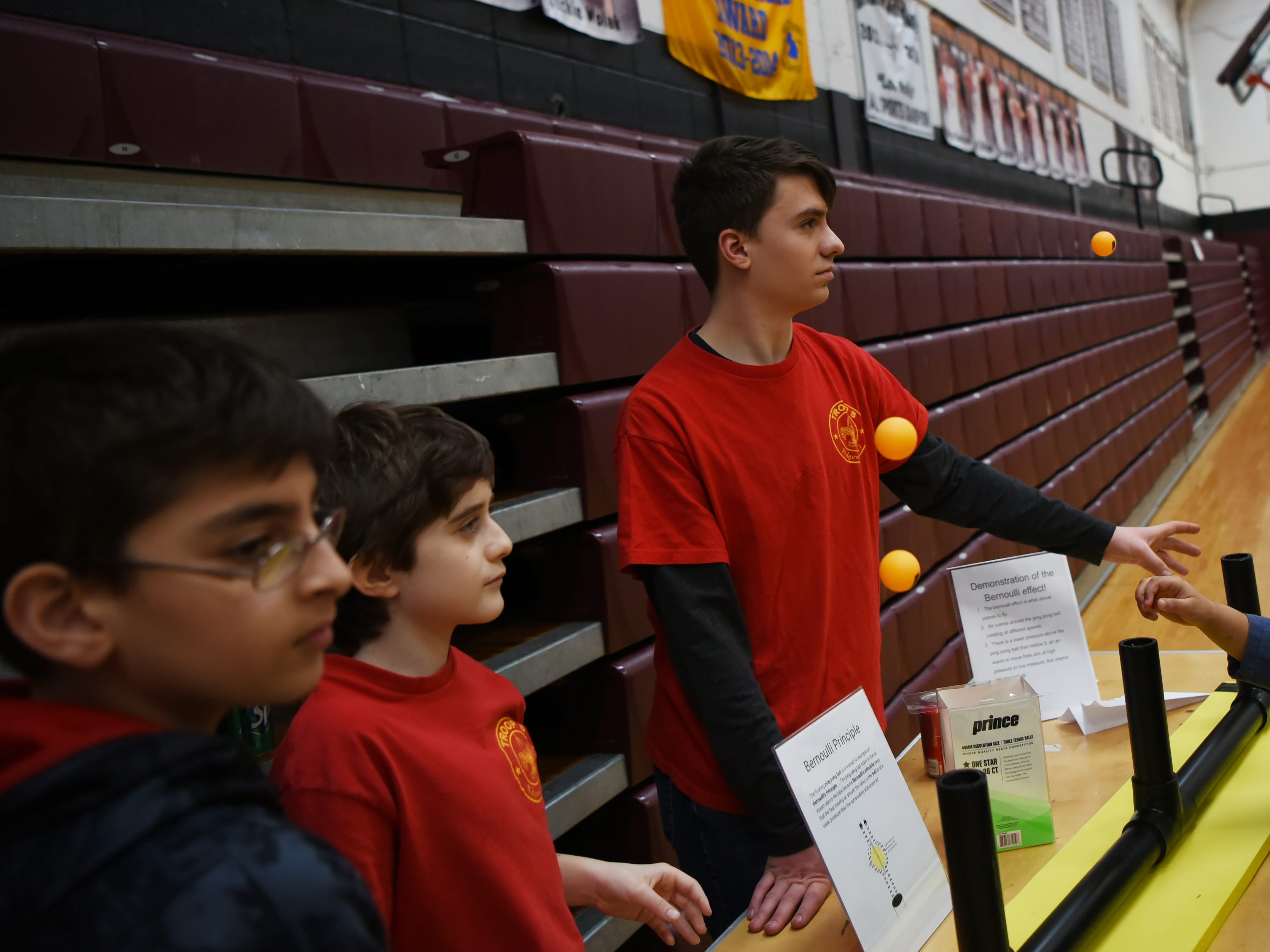 (From left) Anthony Alters, 13, Mario DeAngelin, 12 and Eagle Scout Adam Bock demonstrate the Bernoulli Principle by making ping pong balls float. This is one of the many hands on experiments at the Super Science Saturday held at Ridgewood High School in Ridgewood on Saturday March 2, 2019.