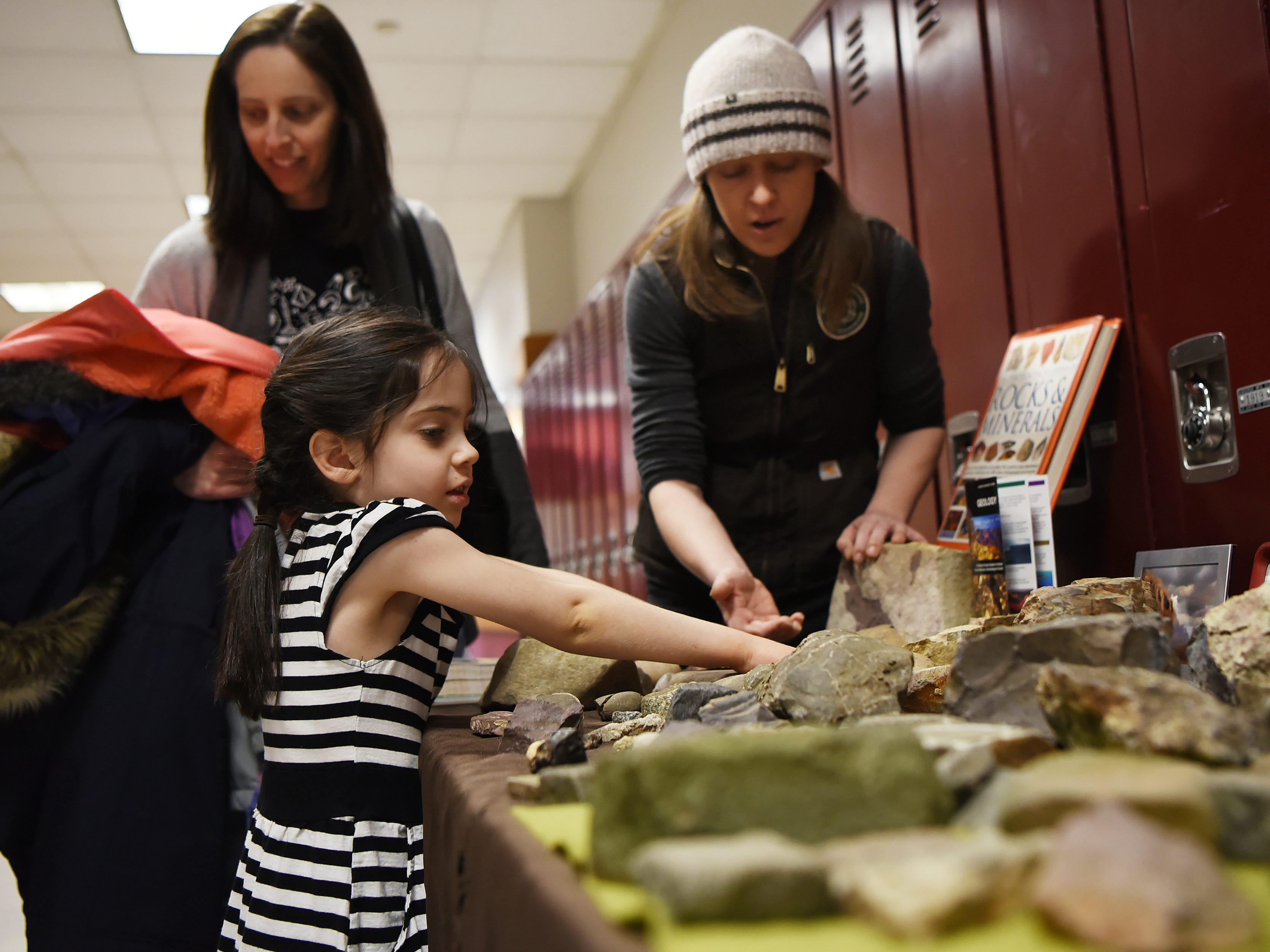 (From left) Candace Lynch and her daughter Margaret Lynch, 5, look at rocks at the 'Geology of the Palisades' table as Christina Fehre shows them some samples. This is one of many hands on activities at Super Science Saturday held in Ridgewood High School in Ridgewood on Saturday March 2, 2019.