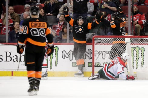 Philadelphia Flyers right wing Travis Konecny, center, celebrates with center Nolan Patrick (19) after scoring a goal as New Jersey Devils defenseman Will Butcher (8) lies in the goal during the second period of an NHL hockey game Friday, March 1, 2019, in Newark, N.J.