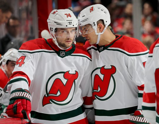 Egor Yakovlev #74  and Connor Carrick #5 of the New Jersey Devils talk during a stop in play in the first period against the Philadelphia Flyers on March 01, 2019 at Prudential Center in Newark, New Jersey.